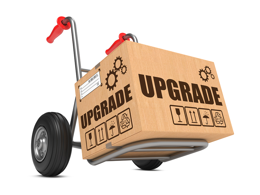 Upgrade Slogan on Cardboard Box on Hand Truck White Background.